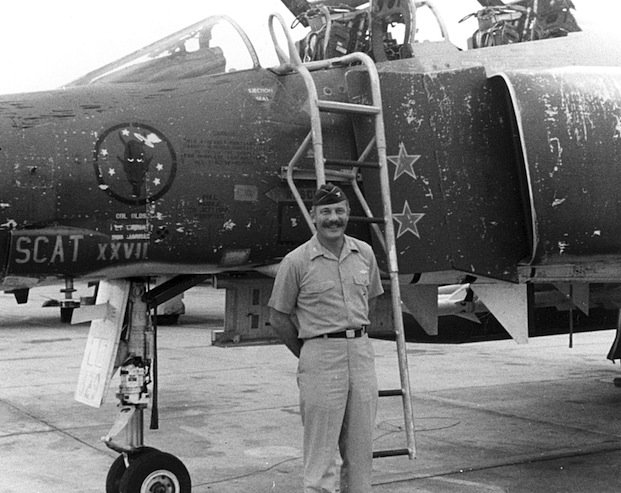 "Col Olds poses beside his Phantom F4 jet with two red stars indicating two North Vietnamese MIG ""kills"". He chalked up a total of four kills before his tour of duty ended."